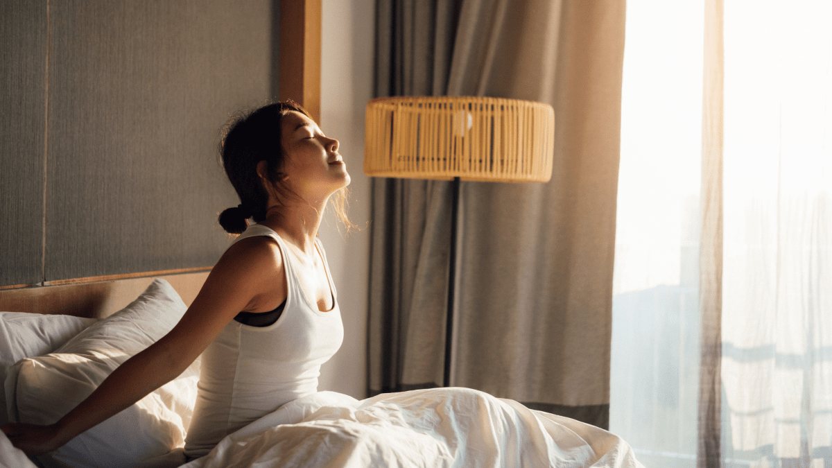 woman waking up smiling in bed learning a language while sleeping