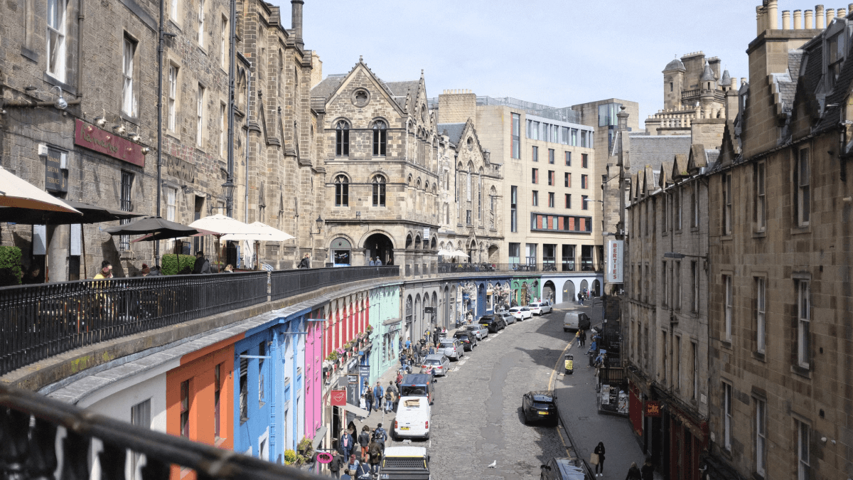 The Scottish accent represented by a street scene in Edinburgh, with large stone buildings on both sides of the street and cars and pedestrians making their way down below