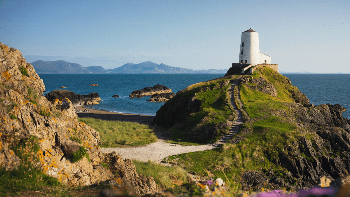 The Welsh accent represented by a lighthouse on a crag of rock on the coast of Wales, looking out on the Ocean to another landmass in the distance