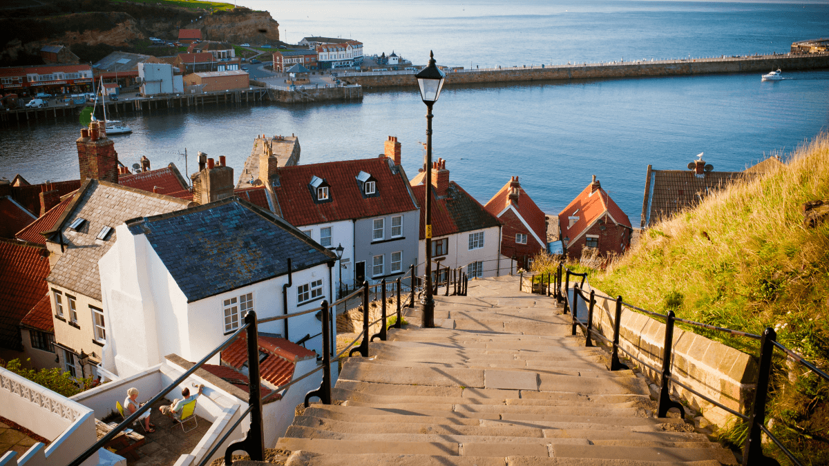 The yorkshire accent represented by a photo taken from the top of a set of outside stairs that looks down a number of English houses, an old-fashioned lamp and the Atlantic Ocean.