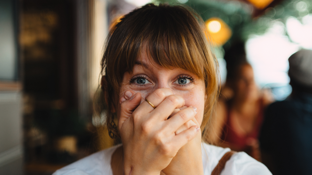 A woman covering her mouth after accidentally using insulting words