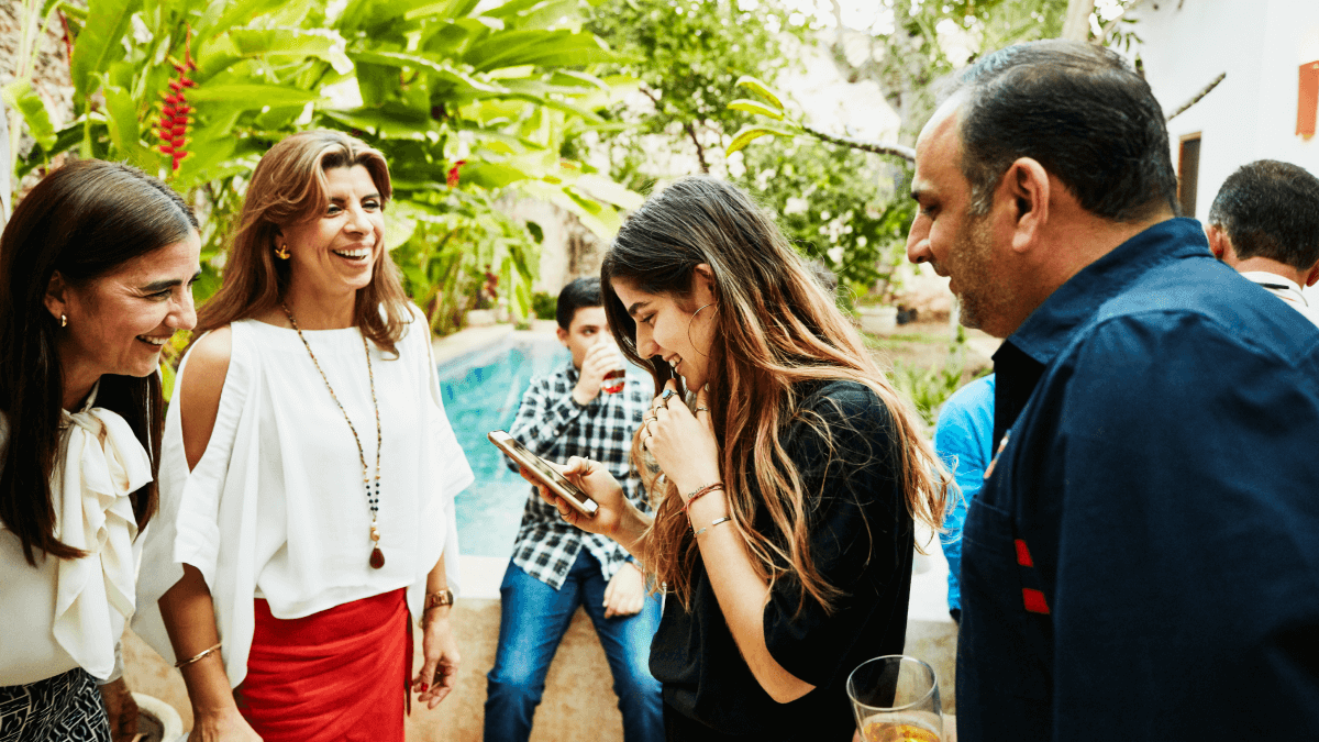 friends laughing in a group outside common spanish verbs