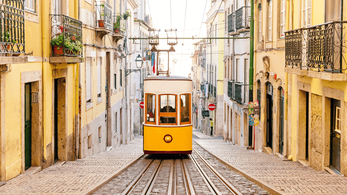 yellow trolley making its way down a street in portugal most spoken languages in europe