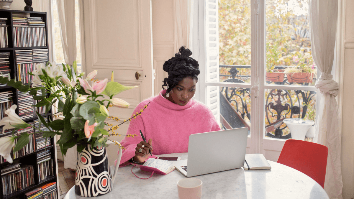 Tips to learn French represented by a woman sitting at a table in her apartment in a bright pink turtleneck/ She's working on her laptop and in the background is a plant and a pair of glass doors looking out onto trees outdoors.