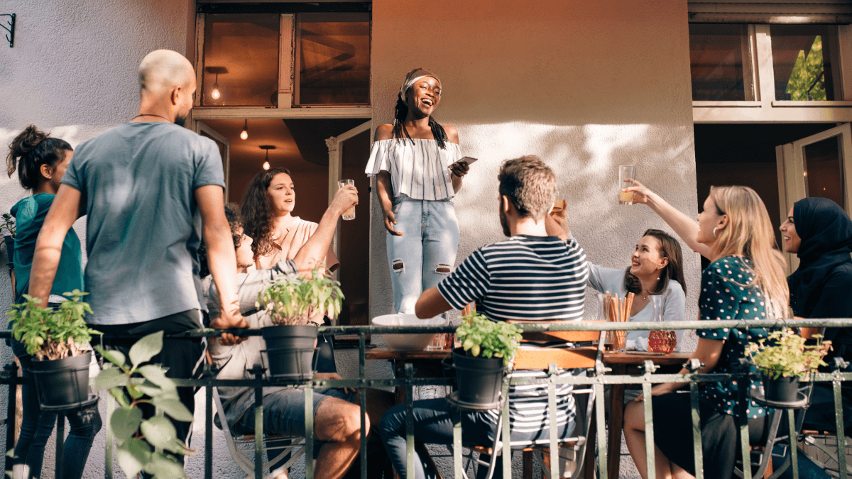 Tips to learn German represented by a group of people, with one woman standing on a chair while laughing and holding her phone, and everyone else is standing or sitting on the ground observing her