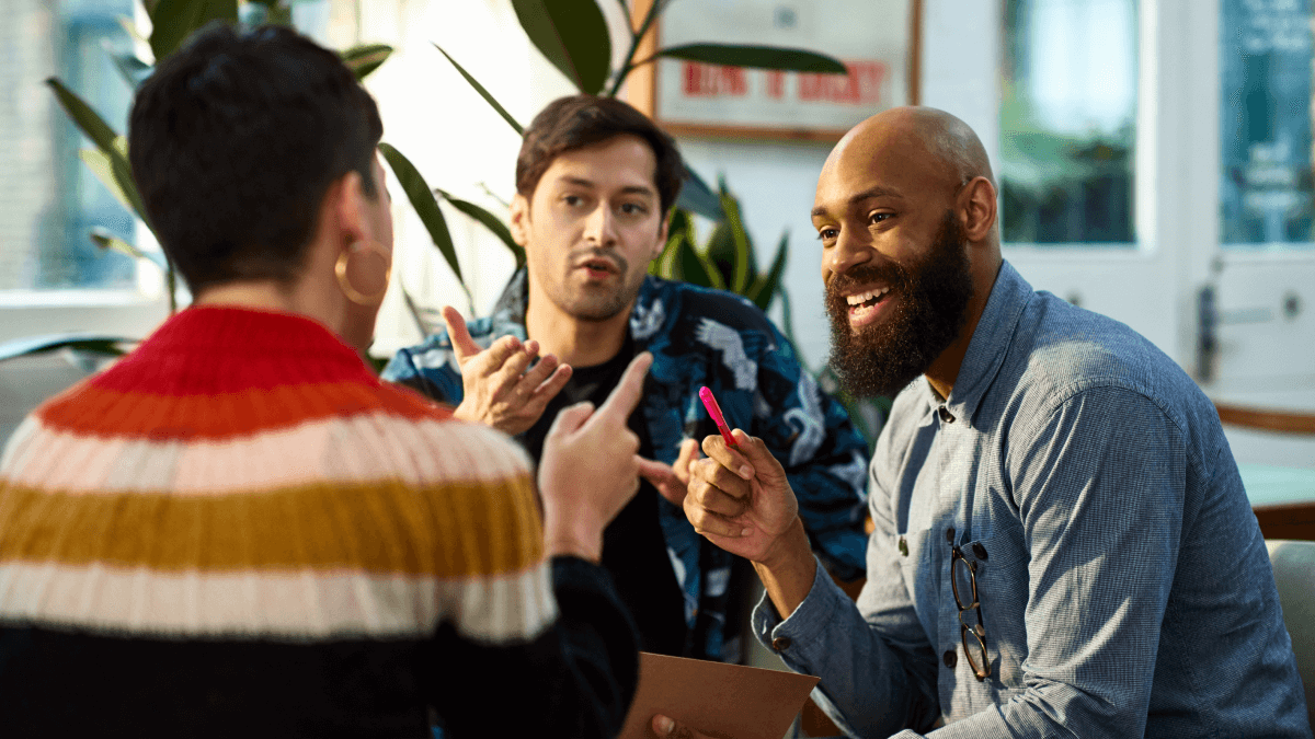 Spanish tips represented by a group of three friends sitting around a table, gesticulating in the air with their fingers as though they're all interrupting each other.