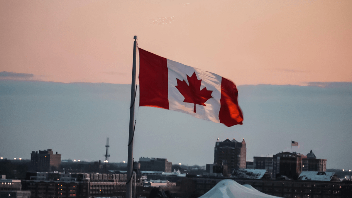 Canadian flag flying over a city to represent Canadian English