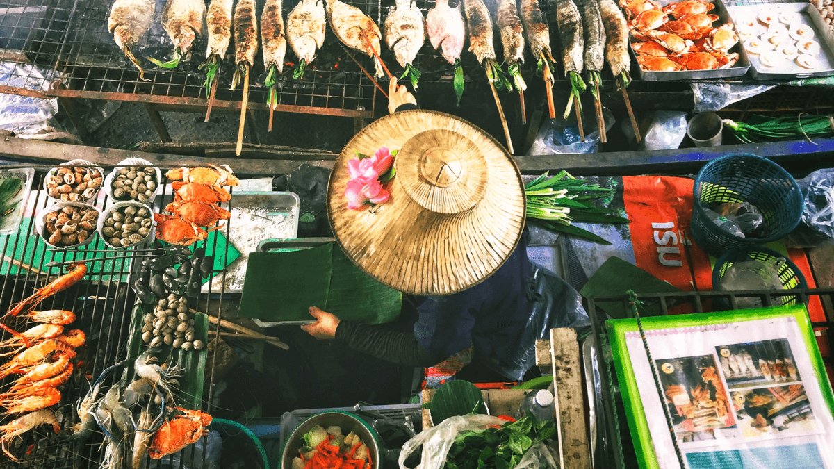 overhead view of Thai street food vendor grilling fish