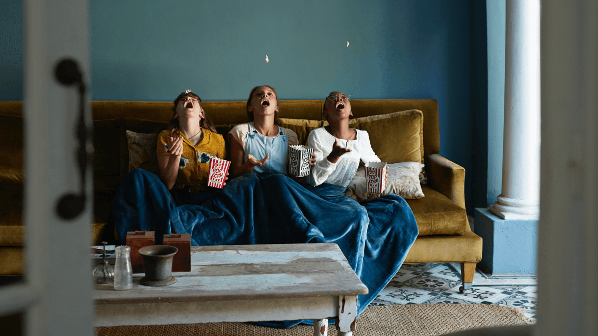 Three women sitting on a couch and throwing popcorn into their mouths and watching movies for language learning