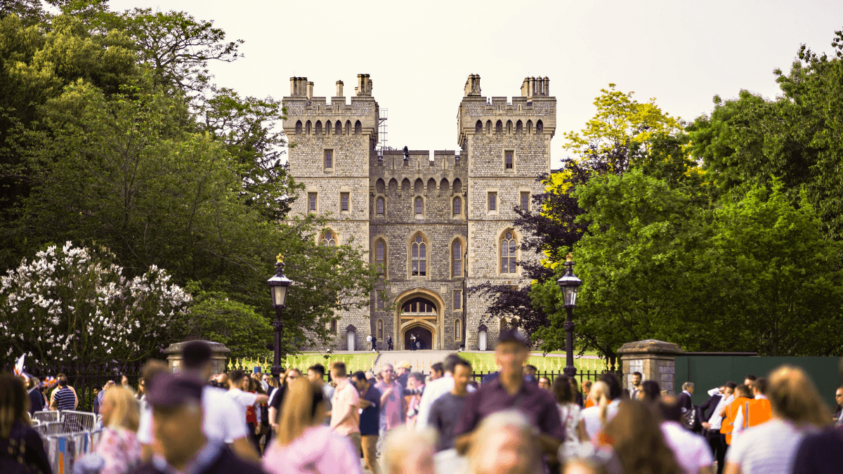 Elizabethan language represented by a modern photo of the turrets at the front of Windsor Castle, in front of which is a large crowd of tourists slightly out of focus.