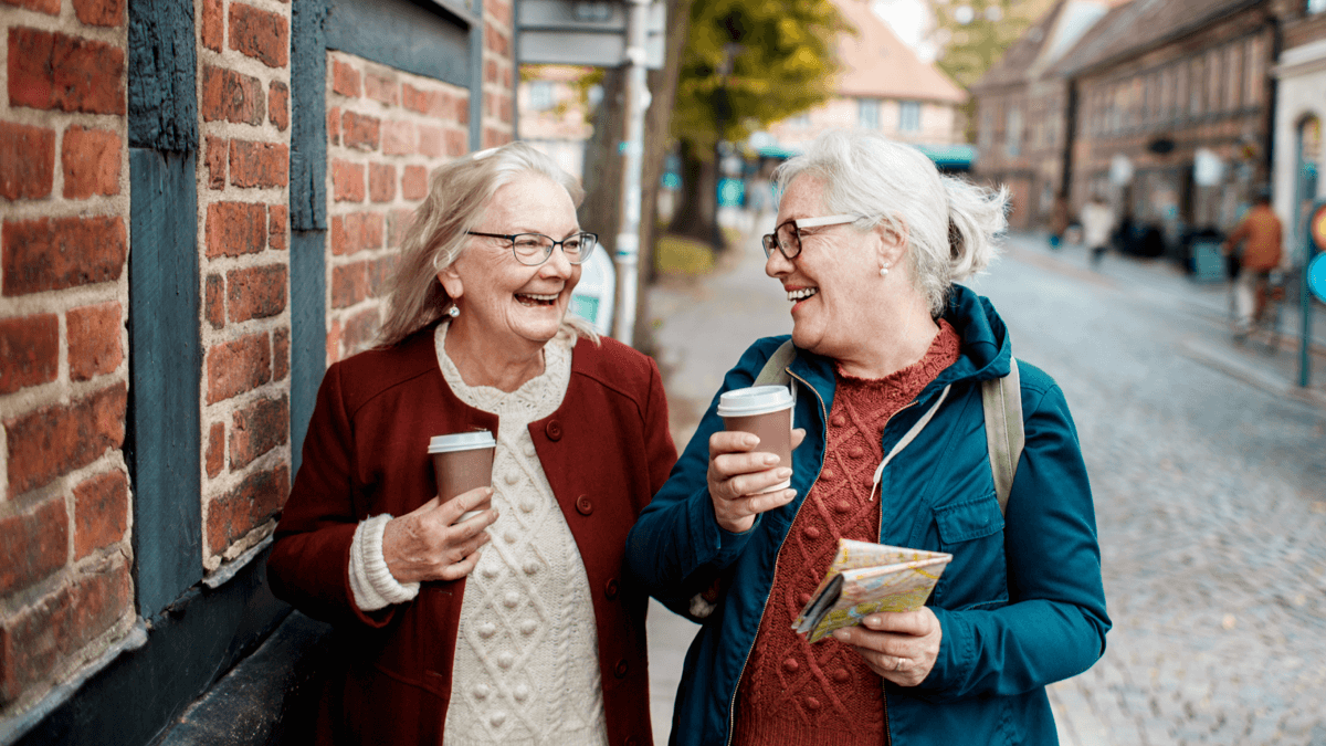 two older white women walking down the street with coffee to represent feelings in Swedish