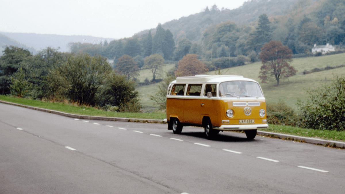 1960s slang represented by a mustard yellow Volkswagen bus driving down a road in the English countryside