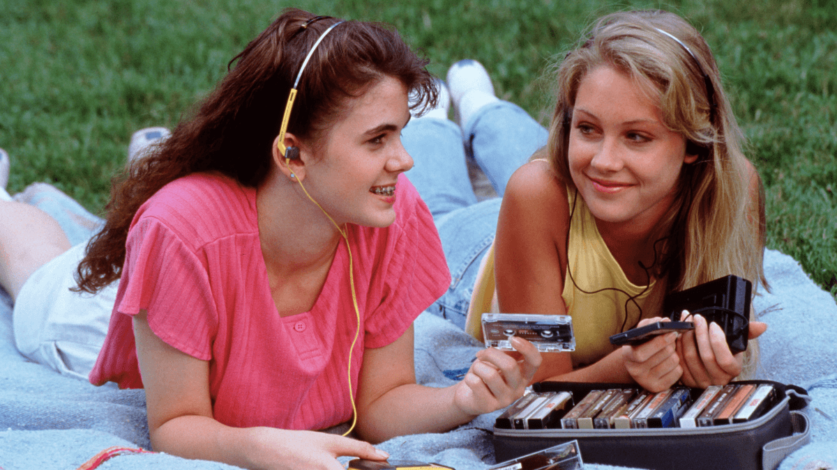 1990s slang represented by two girls wearing neon and looking through a case of cassettes while lying on a picnic blanket in the park