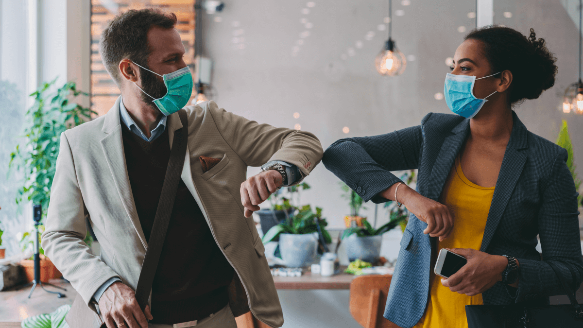 man and woman elbow bumping wearing masks in coffee shop distance learning