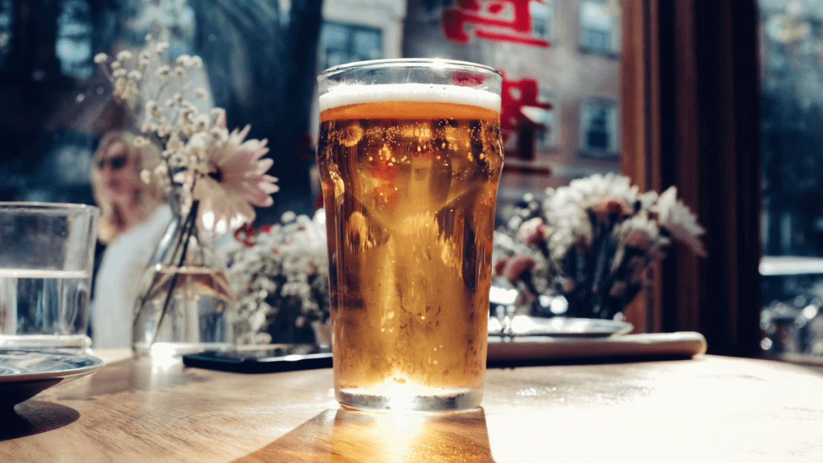 beer with sunlight shining through it and flowers on nearby tables norwegian pronunciation