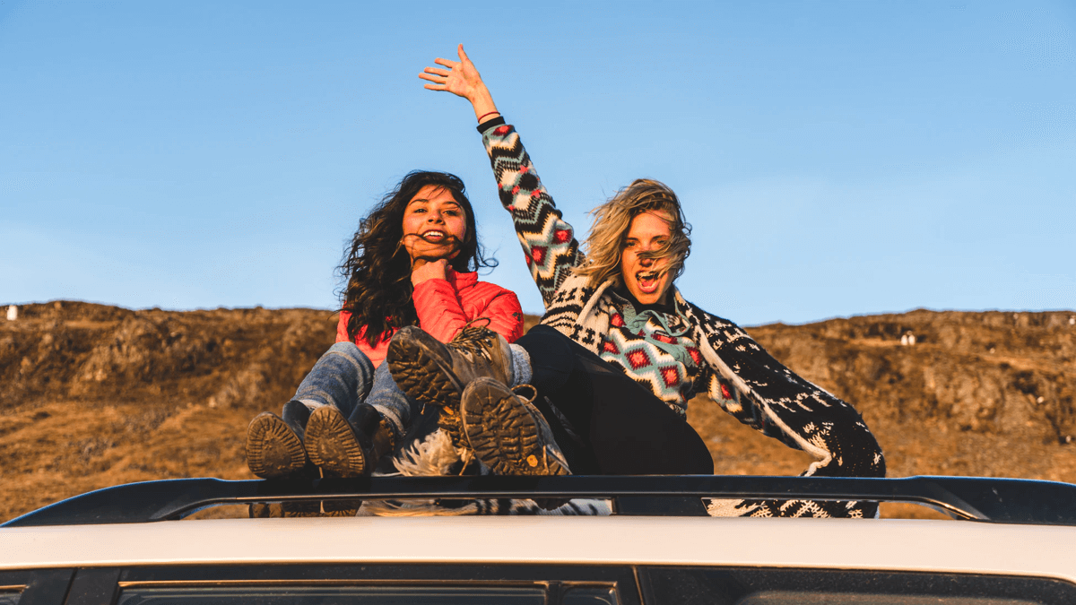 two women sitting on roof of car and waving saying goodbye in swedish
