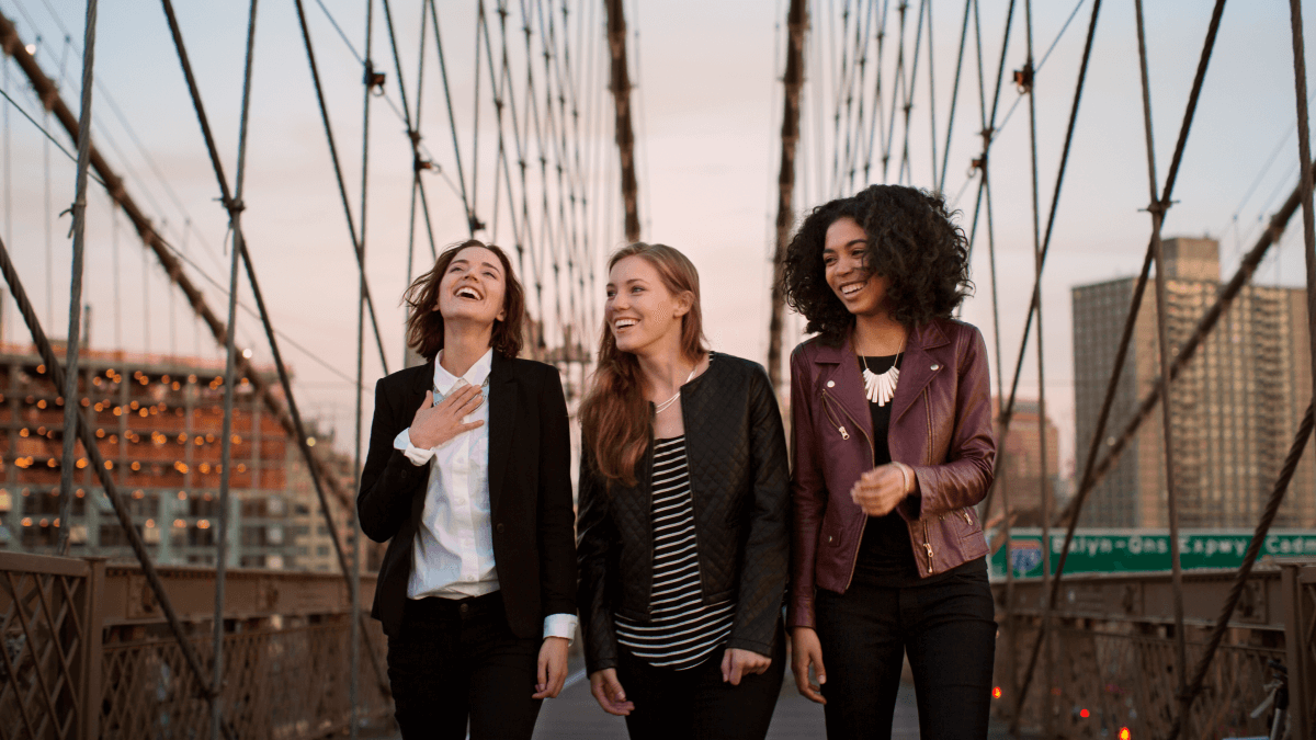 trio of young women laughing and walking over bridge accent reduction