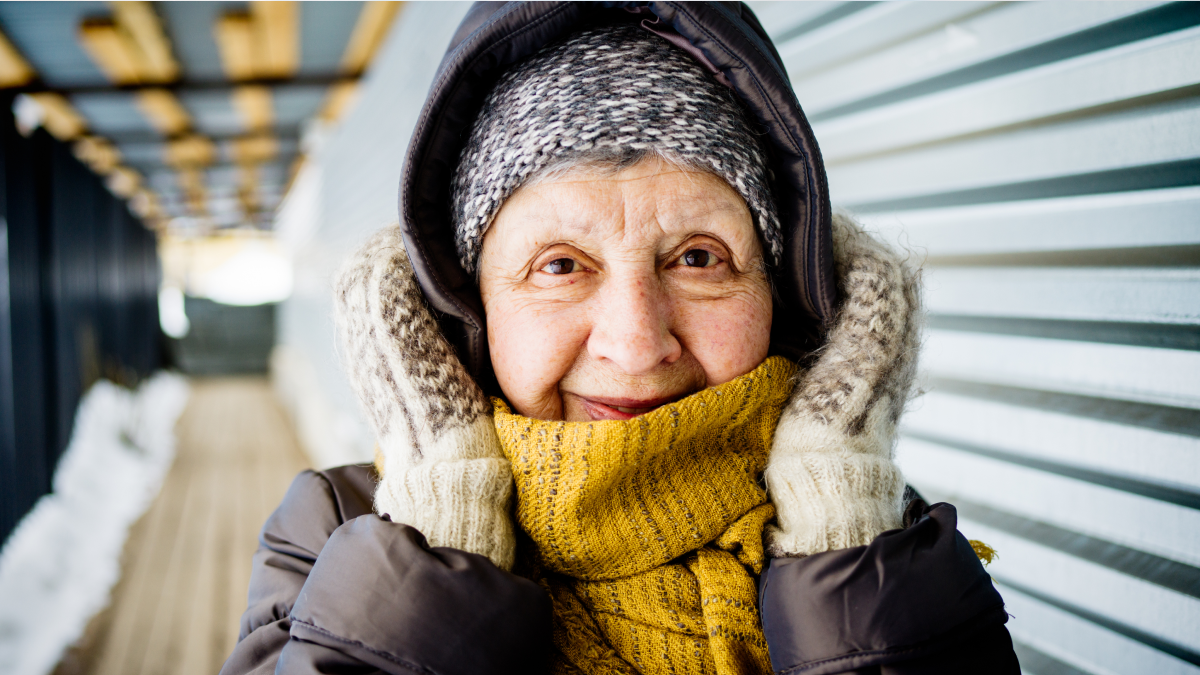 Senior woman bundled up in scarf and warm clothing - how people survive winter