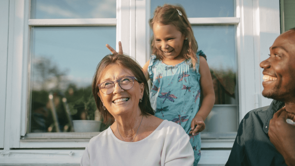 little girl giving bunny ears to grandma and dad smiling family in swedish