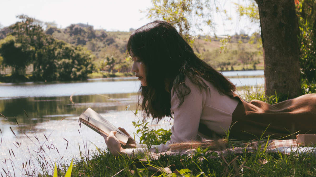 A woman by a lake reading one of the most translated books in the world