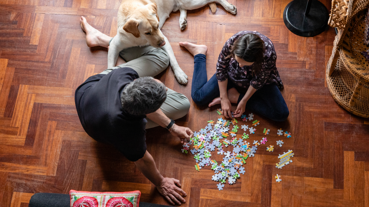 A couple and their dog doing a puzzle to represent the parts of speech