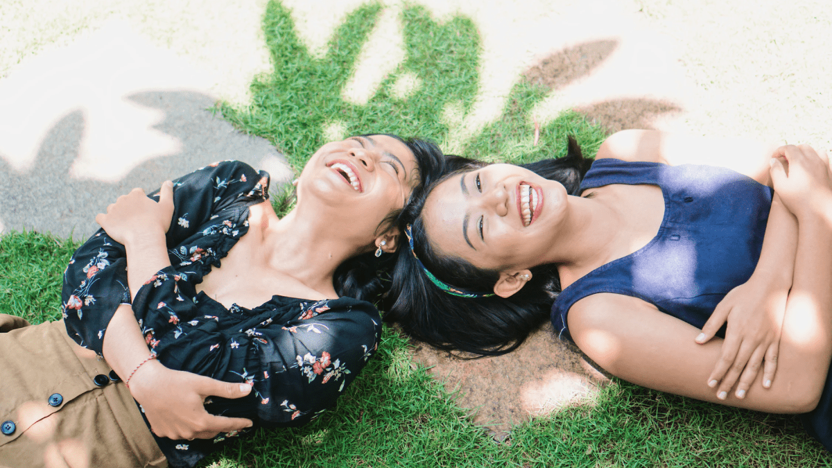 two women lying on their backs on the grass laughing why learn indonesian