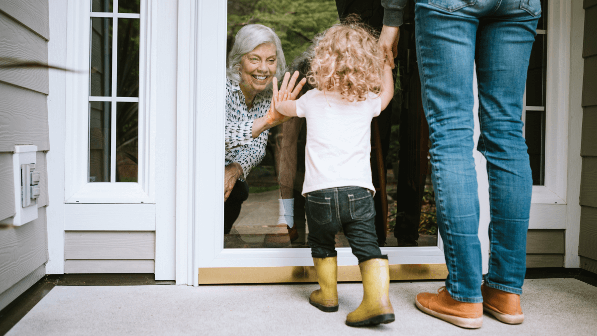 grandma waving to grandchild through glass door goodbye in norwegian