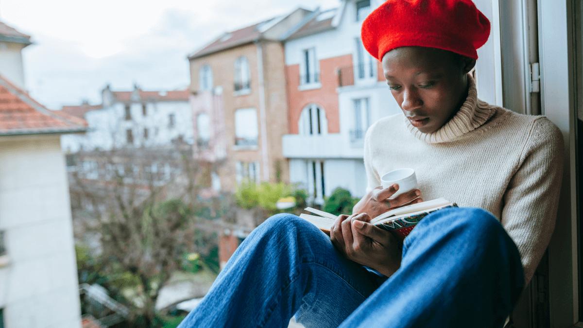 a bookstagrammer reads on a windowsill