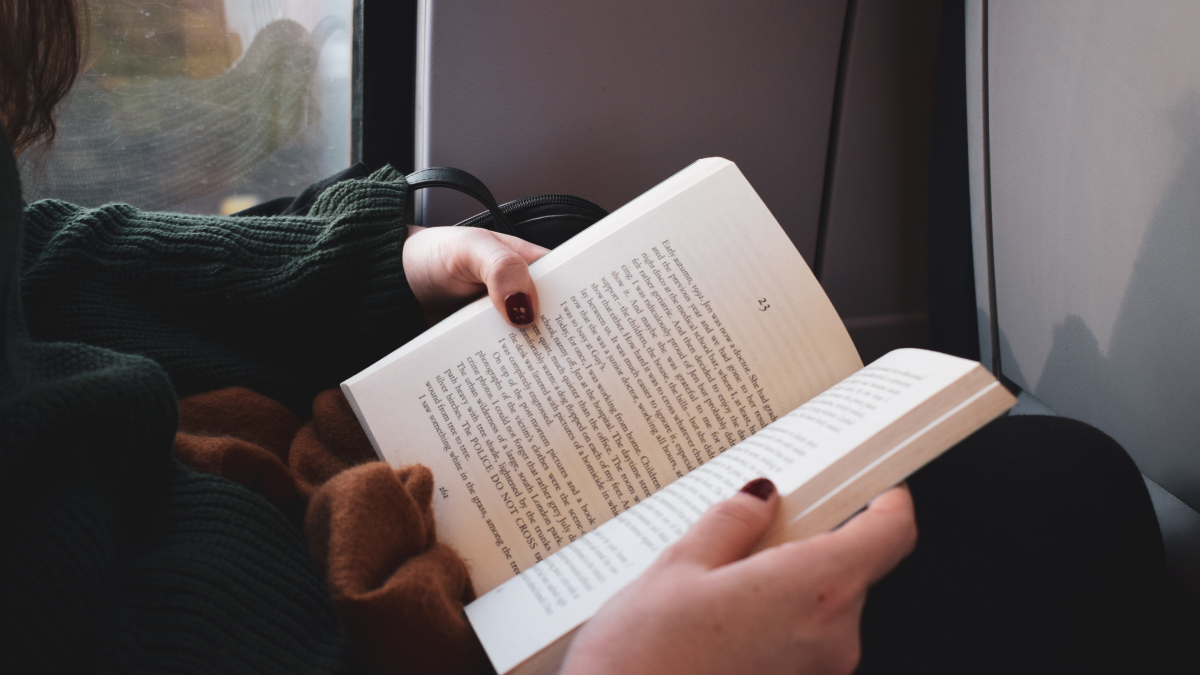 person holding book open right to left languages