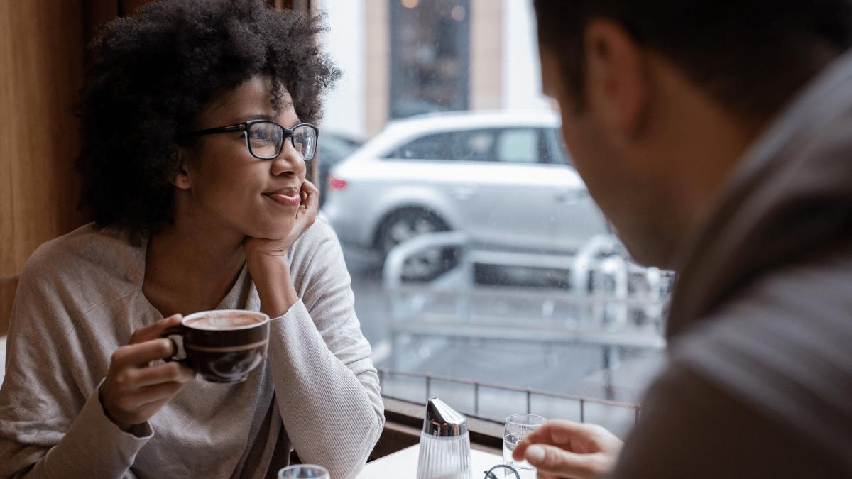 woman enjoying a coffee near a cafe window with a friend austrian german