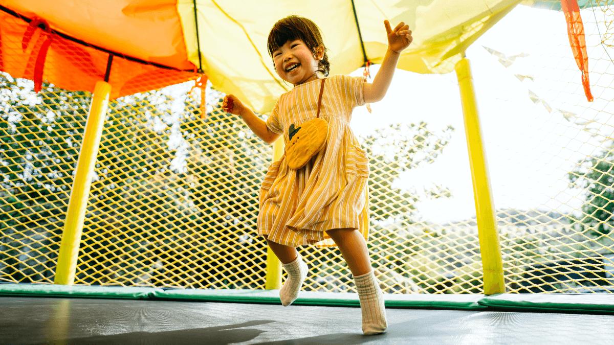 little girl in yellow dress bouncing on trampoline practice german