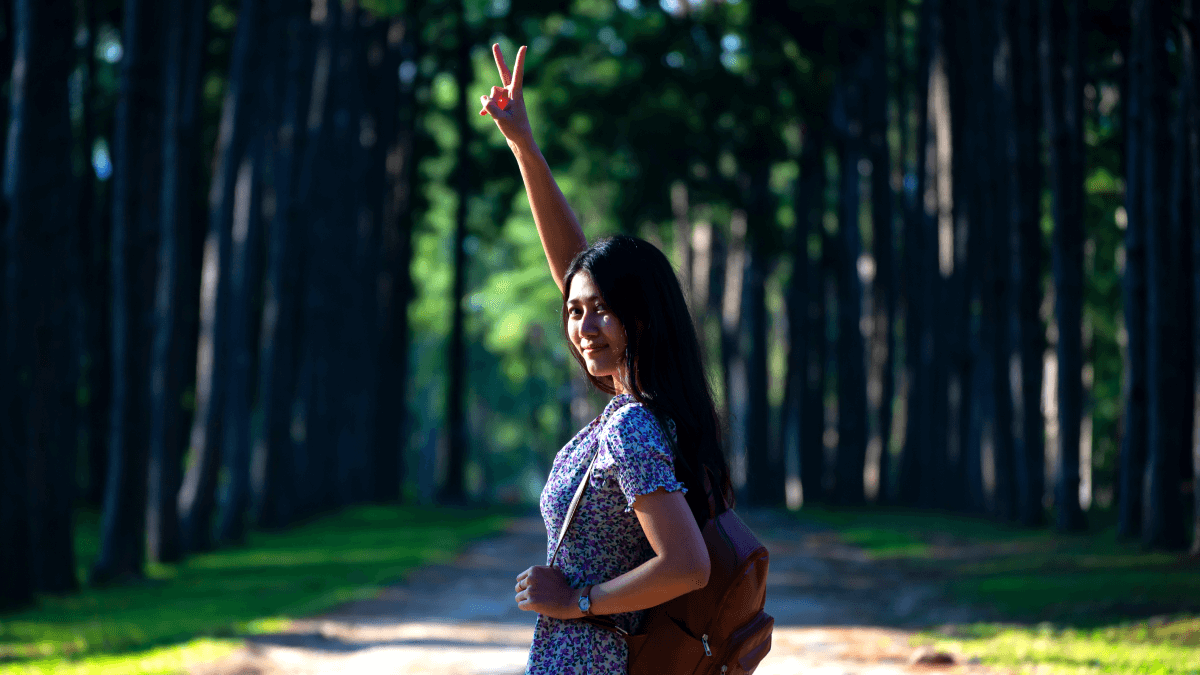 woman waving goodbye with peace sign with forest in the background goodbye in indonesian