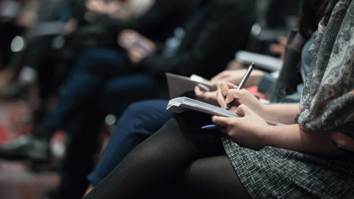 Journalists writing in notebooks maybe using Teeline shorthand