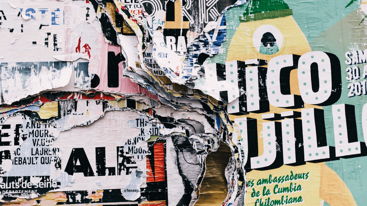 closeup of torn advertisements on a wall why is language important