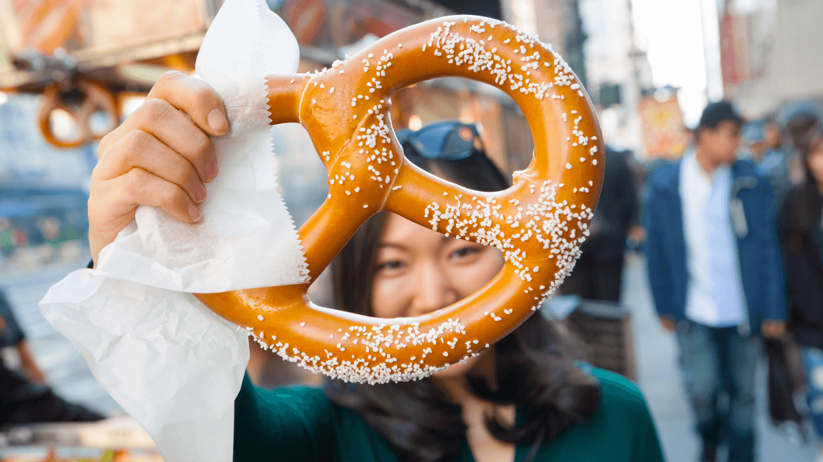 A woman holding a soft pretzel which is one of many English words that are actually German
