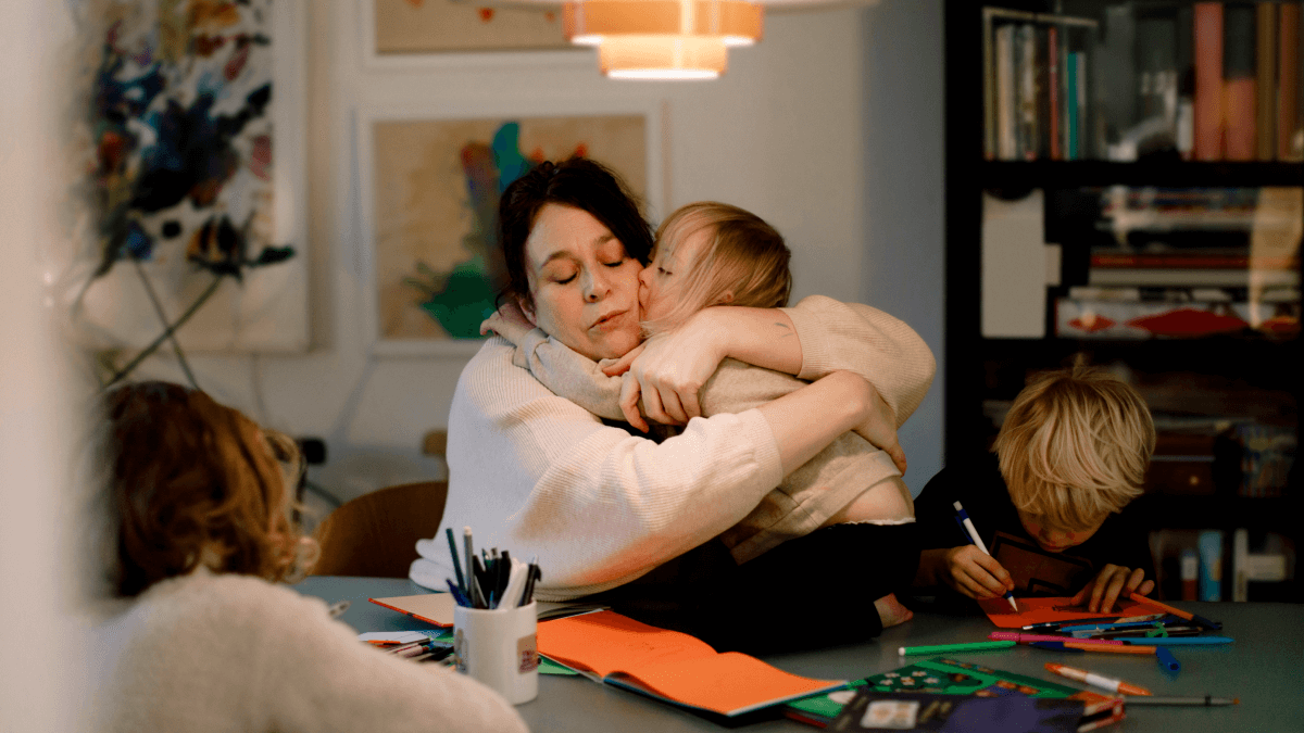 mom hugging little girl with other kids sitting around the table sorry in swedish