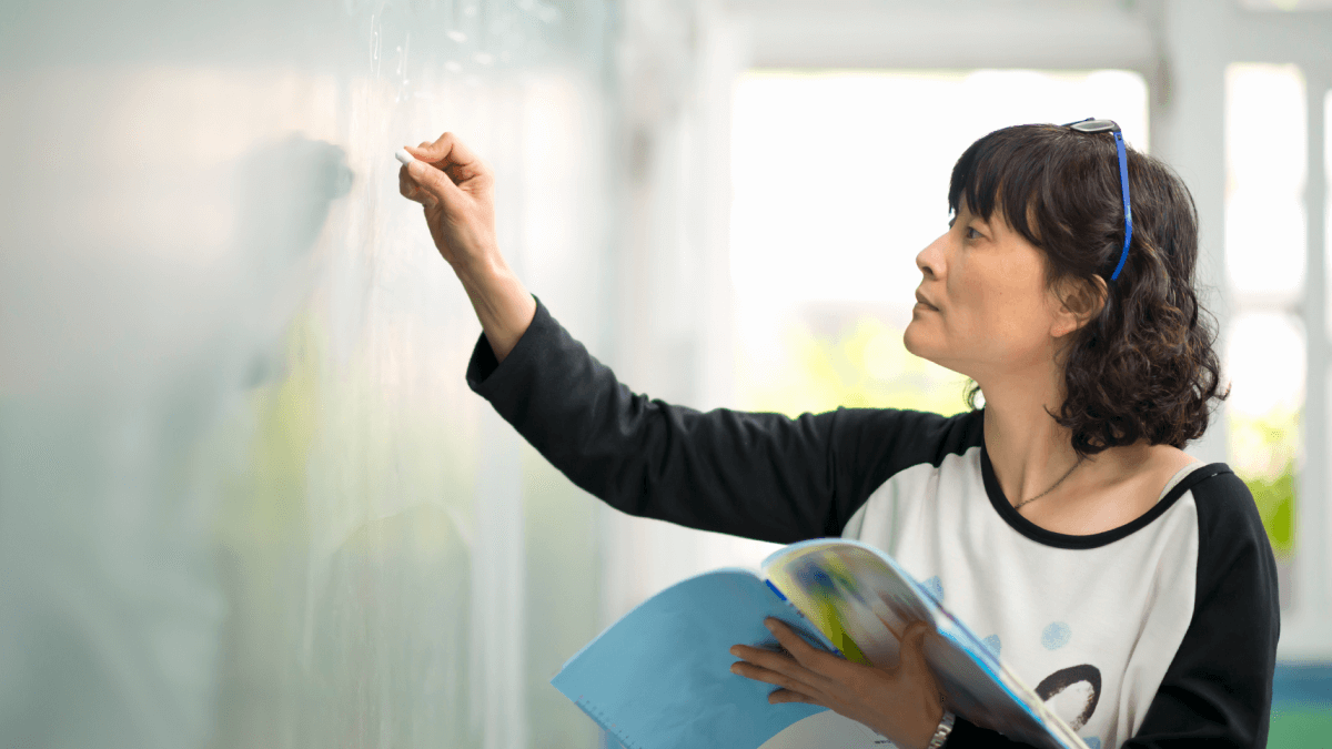 A woman writing on a chalkboard to represent learning a language from scratch