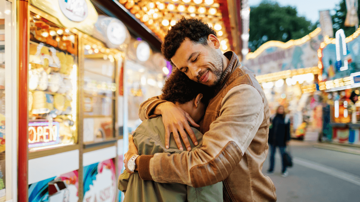two people hugging at a carnival sorry in portuguese