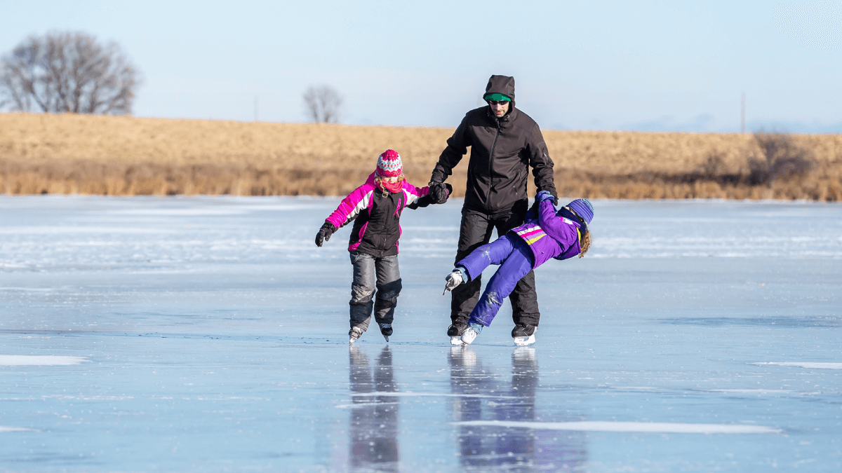 adult holding children's hands while they ice skate and one of them slips russian learners