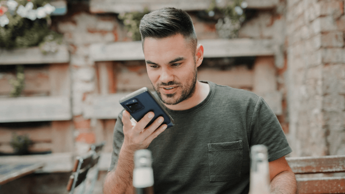 A man at a restaurant talking to one of his voice assistants on his phone