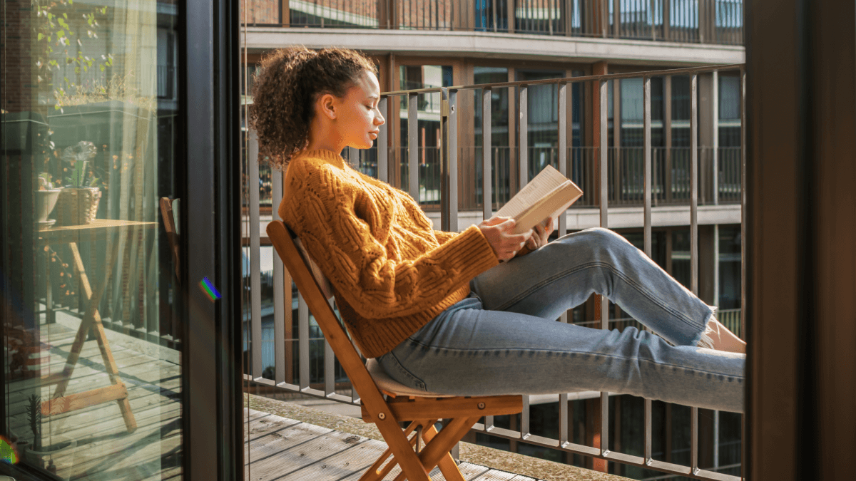 A young woman learning German modal verbs by reading a book on the balcony in a wooden chair, wearing long blue jeans and a yellow sweater, with her hair up in a ponytail.