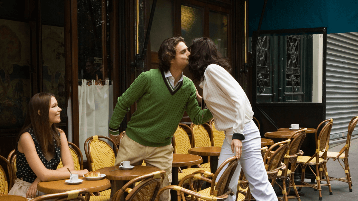 two friends giving a cheek kiss or la bise over the table outside