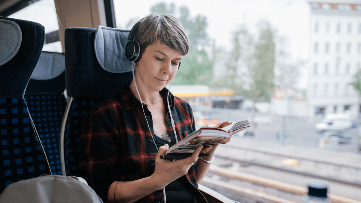 woman on train with headphones in reading a book german cases