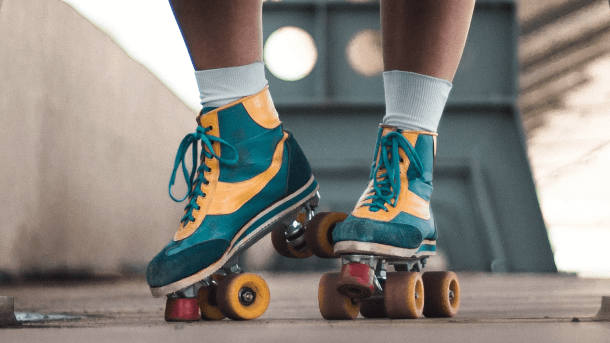 A pair of mustard yellow and teal roller skates to represent 1980s slang