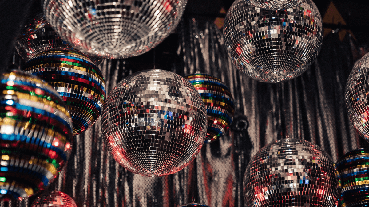 1970s slang represented by eight disco balls handing in a dimly lit room, with lights shining all around.