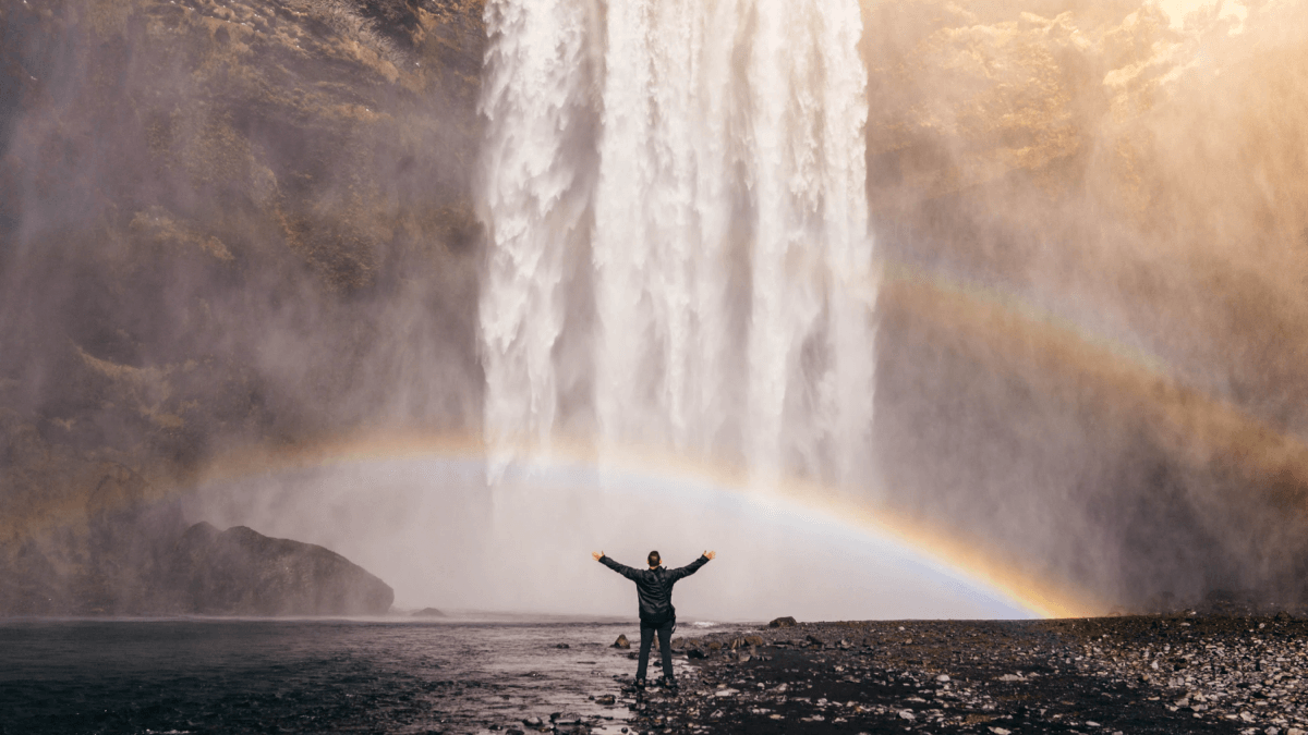 Colors in other languages represented by a man standing far away, in front of a wide waterfall that is creating a rainbow in the air above him.