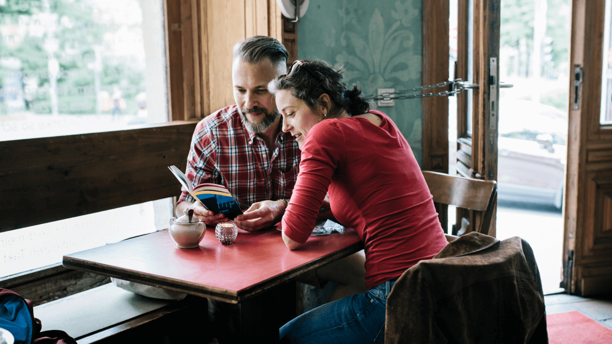 A middle-aged man and woman learning French modal verbs by reading a book while sipping coffee and sitting at a red table.