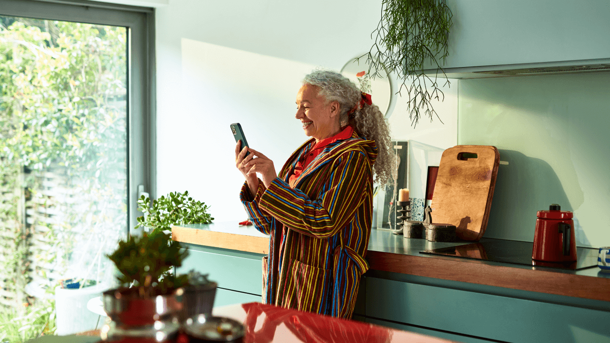Italian modal verbs represented by a gray-haired woman standing in her well-lit kitchen, using her phone.