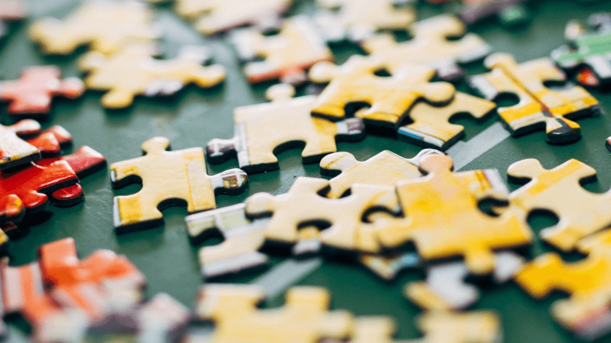 prefixes, suffixes and infixes represented by a closeup of a scattering of yellow and red puzzle pieces on a green table