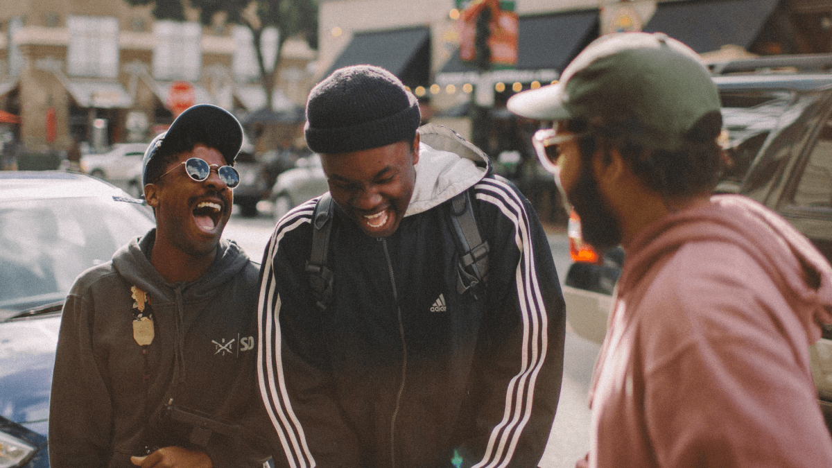 three guy friends cracking up together on the street small talk in english